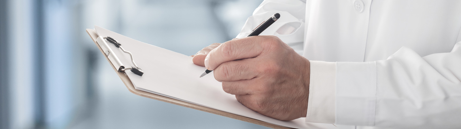 Male doctor holding clipboard filling up medical form
